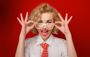 Surprised woman looking you above eyeglasses, isolated on red