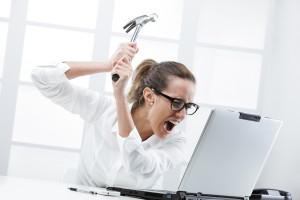 Freaked out business woman with a hammer ready to smash her laptop computer